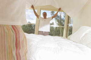 Mature couple making bed, focus on man holding bed sheet in background, smiling